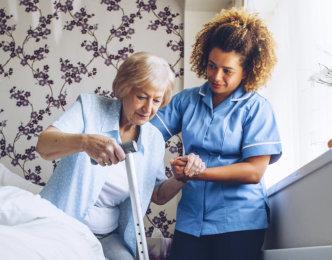 caregiver helping senior woman get up