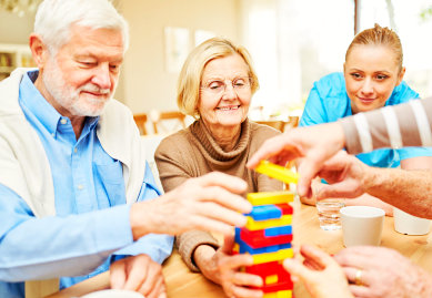 caregiver and seniors playing with blocks