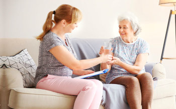 caregiver giving senior woman her medication