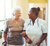 caregiver and senior woman walking together