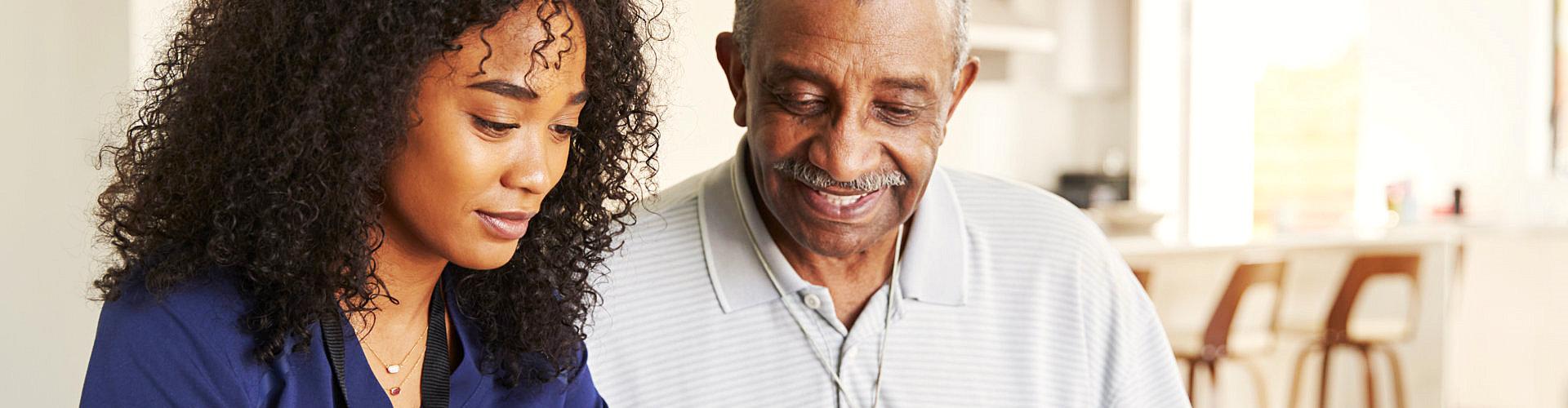smiling senior man and caregiver
