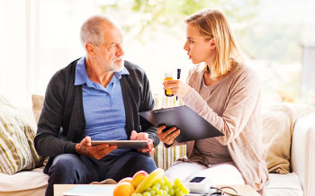 caregiver reminding senior man about his medicine