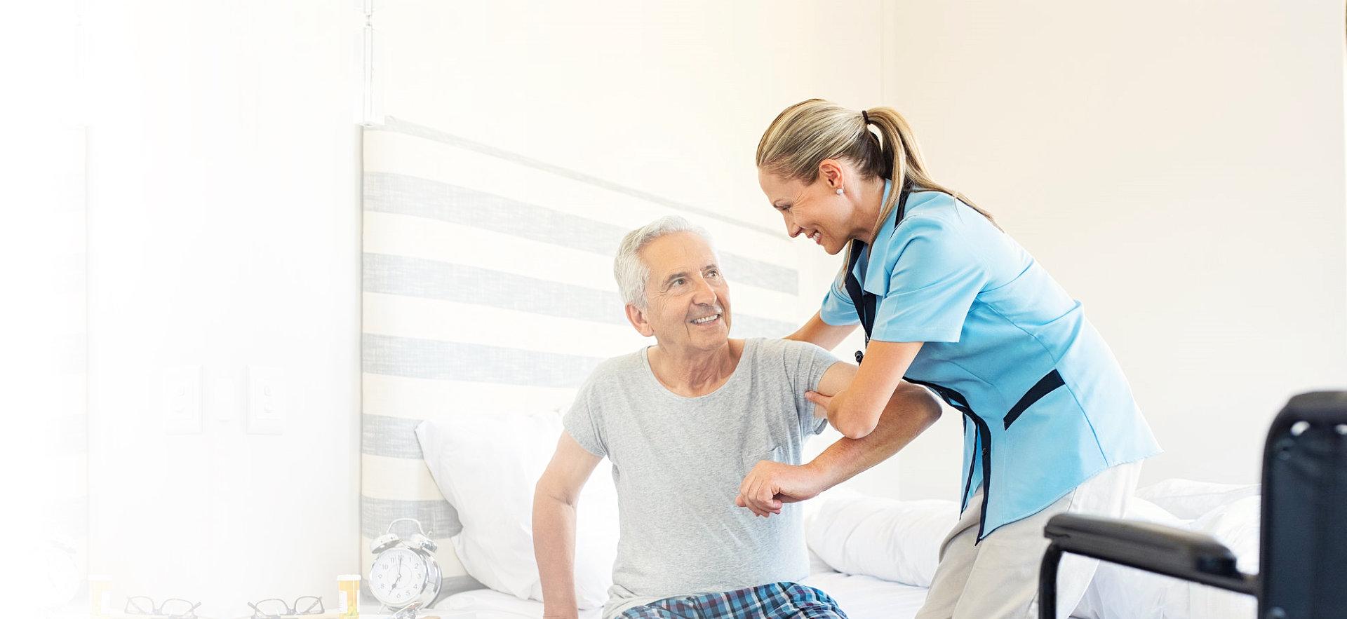 caregiver helping a senior man get up