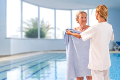 caregiver giving towel to a senior woman after bath