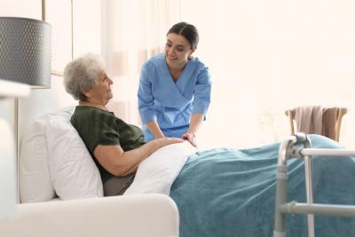 caregiver helping senior woman go to sleep