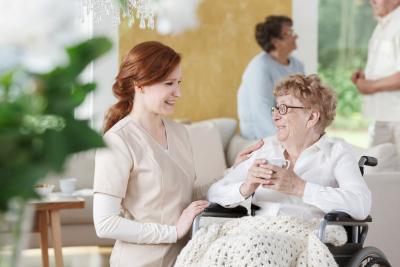 caregiver and senior woman on wheelchair having a conversation