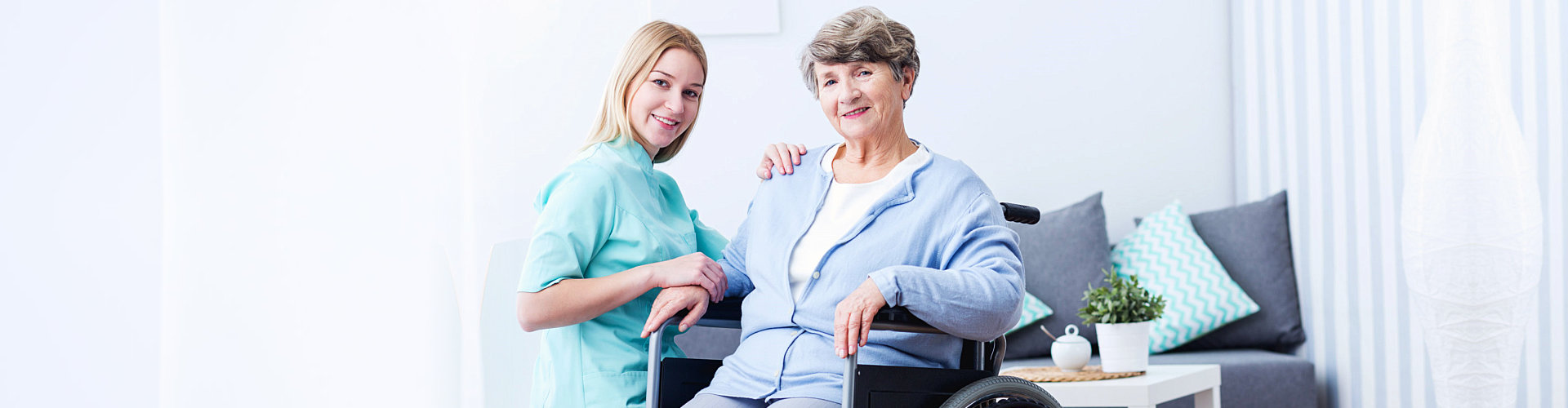 smiling senior woman on wheelchair with her caregiver